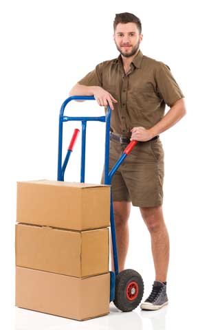 Delivery guy in brown uniform with a dolly that has 3 brown cardboard boxes on it.